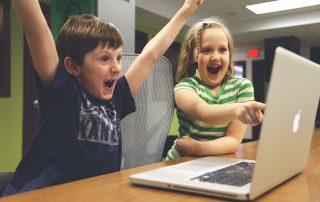 Kinderen spelen achter laptop