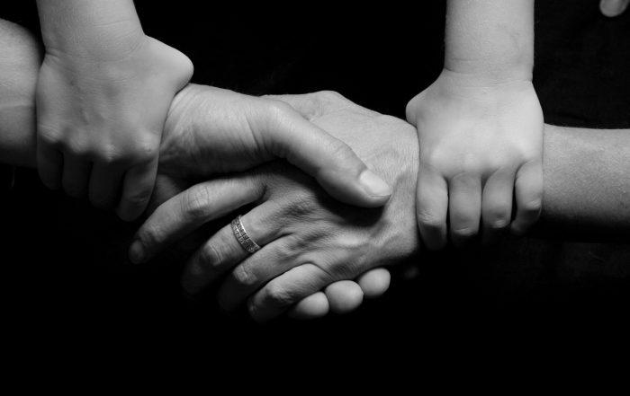 Ouders en kind houden hand vast