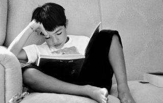 Kind leest boek op bank